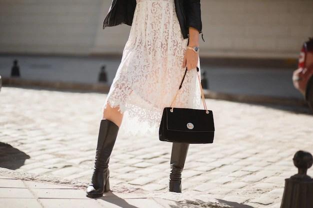 Pernas de uma jovem mulher bonita com botas andando na rua com roupa da  moda, segurando bolsa, vestindo jaqueta de couro preta e vestido de renda  branca, estilo primavera outono | Foto