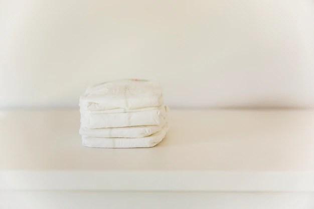 Pilha de fralda de cachorro em mesa e fundo branco