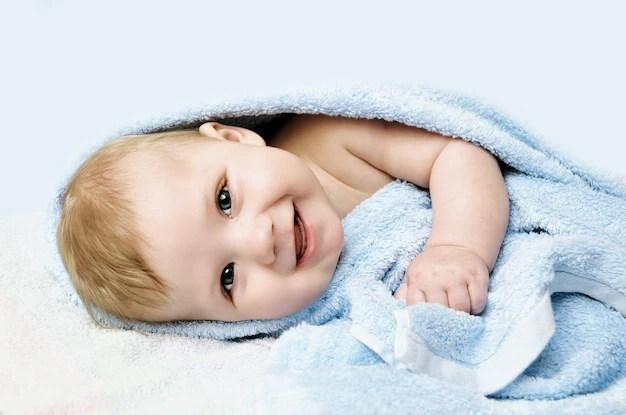 Bebê sorrindo e enrolado em toalha de banho