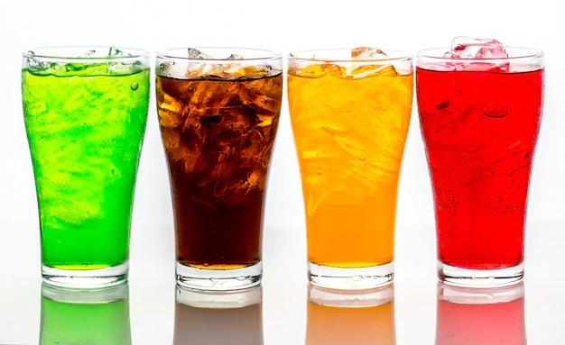 Quatro copos de refrigerantes coloridos com gelo em fundo branco