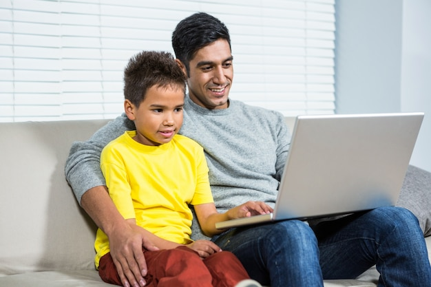 Pai e filho usando computador juntos e conversando