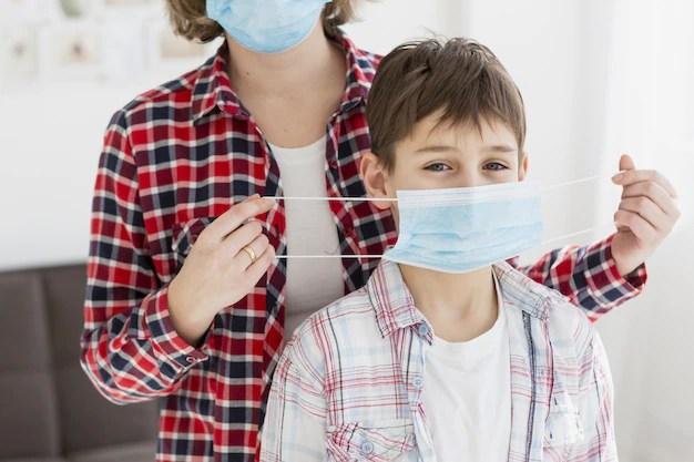 Mãe colocando máscara de proteção em filho reabertura de comércio pandemia coronavírus