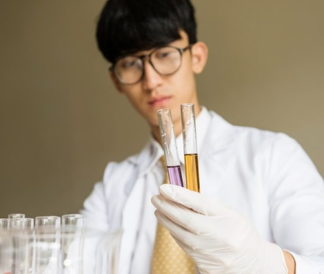 Asian Male Scientist Holding Test Tube With Chemical Liquid Premium Photo