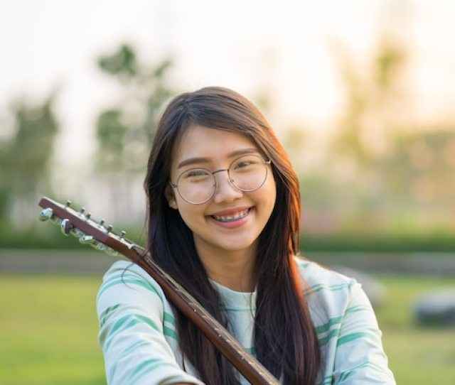 Asian Teen Girls With A Guitar At The Shoulder In The Lawn Premium Photo