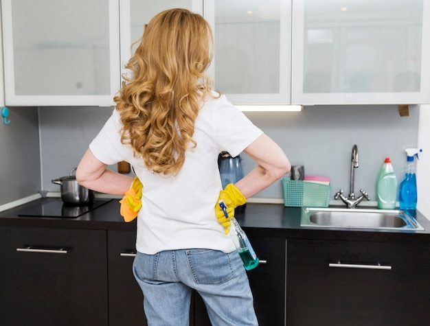 Back view of woman cleaning the kitchen Free Photo