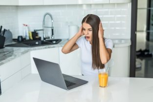 Beautiful shocked excited young student girl sitting indoors using laptop computer Free Photo