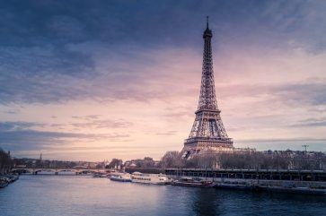 Beautiful wide shot of eiffel tower in paris surrounded by water with ships under the colorful sky Free Photo