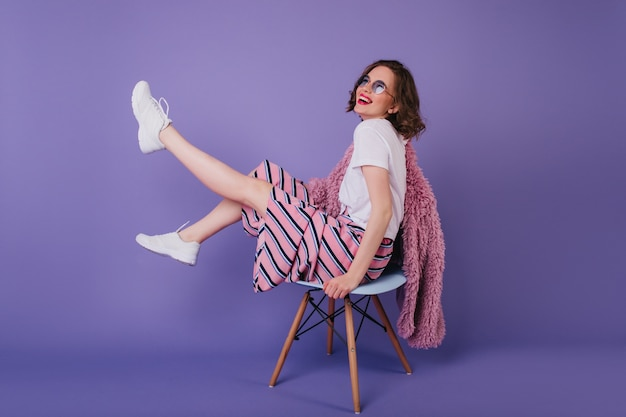 Blissful young lady in sunglasses fooling around during photoshoot on chair. laughing winsome girl in white shoes. Free Photo
