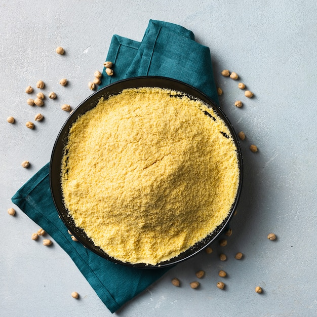Chickpea flour in black ceramic bowl on light background top view with copy space Premium Photo