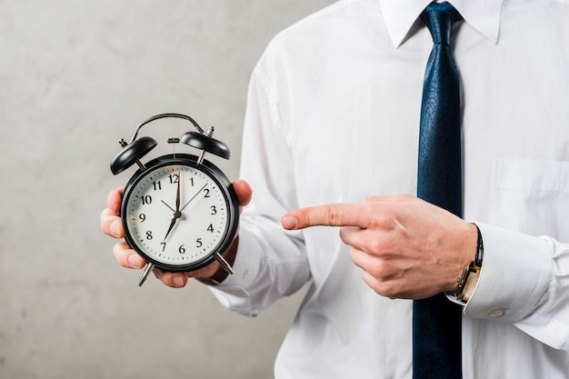 Close-up of a businessman pointing the finger at time against grey wall Free Photo