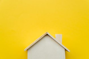Close-up of wooden miniature house model on yellow background Free Photo