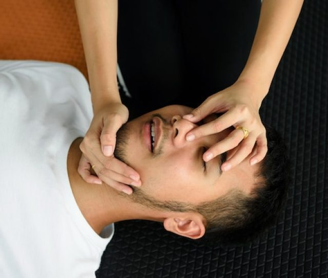 Closeup Of Unconscious Asian Man And Female Hands Holding His Nose And Opening Mouse Premium Photo