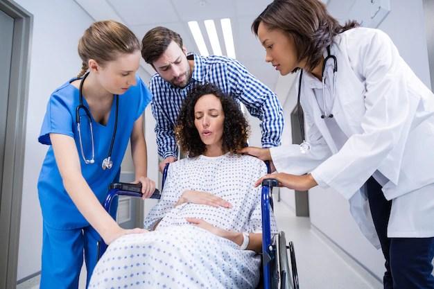 Gestante em cadeira de rodas sendo levada por equipe de saúde e acompanhante em corredor hospitalar