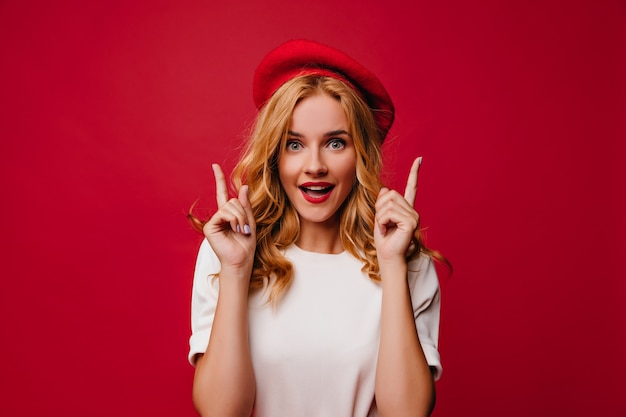 Ecstatic white girl in beret posing with amazement. elegant caucasian female model in t-shirt standing on red wall. Free Photo