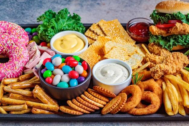 ファーストフードの品揃え。ジャンクフードのコンセプトです。心臓、歯、皮膚、体に不健康な食べ物。 | プレミアム写真