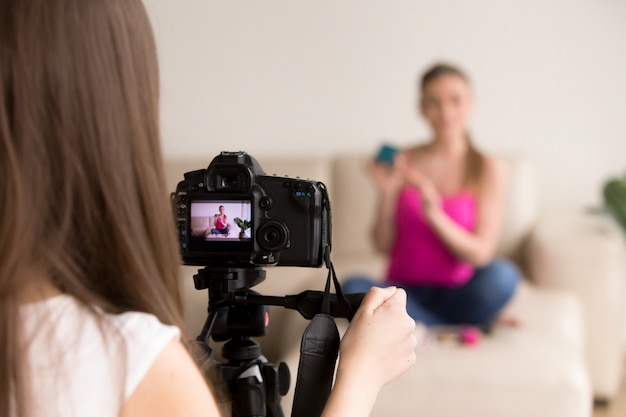 Female photographer taking photo of girl on sofa. Free Photo