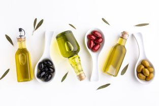 Flat lay yellow red black olives in spoons  with leaves and oil bottles Free Photo