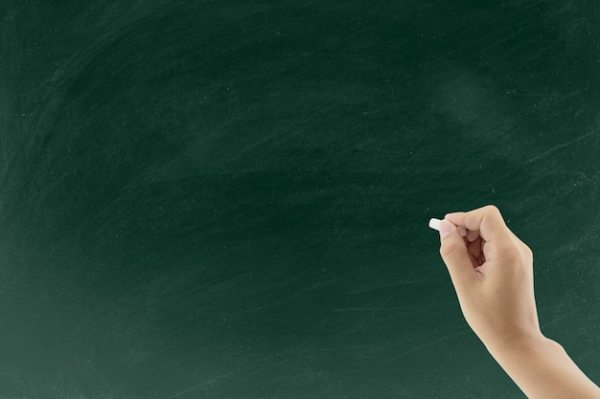 Hand holding white chalk and starting to write on ...