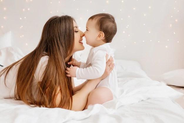 Mãe e bebê brincando em cama