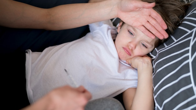 High view sick child with fever Free Photo