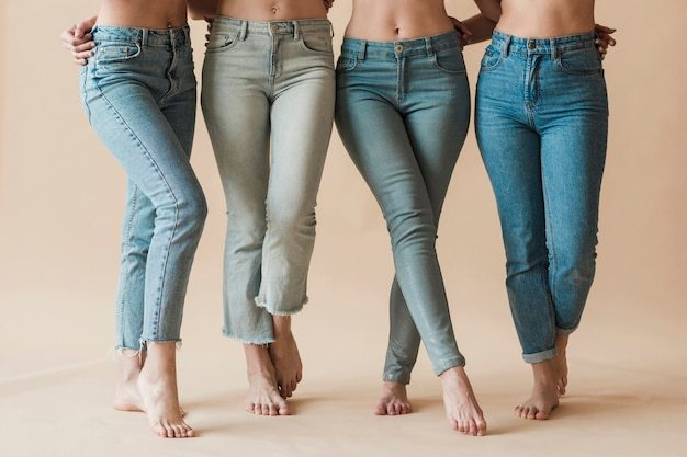 Legs of female group wearing jeans standing in different poses Premium Photo
