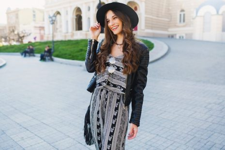 Lifestyle portrait of pretty cheerful woman enjoying holidays in old european city. street fashion look. stylish spring outfit. Free Photo