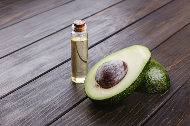 Little bottle with oil and avocado stand on the wooden table Free Photo