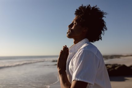 Man performing yoga on the beach Free Photo