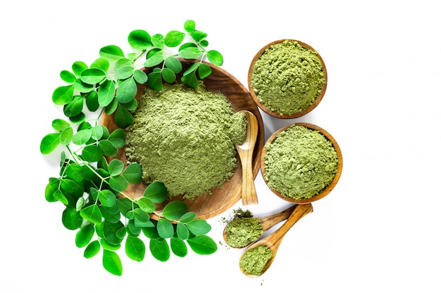 Moringa powder (moringa oleifera) in wooden bowl with original fresh moringa leaves isolated Premium Photo