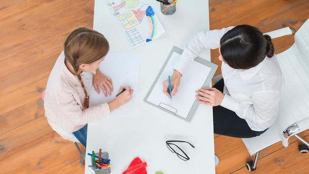 An overhead view of female psychologist making note sitting with the girl drawing on paper Free Photo