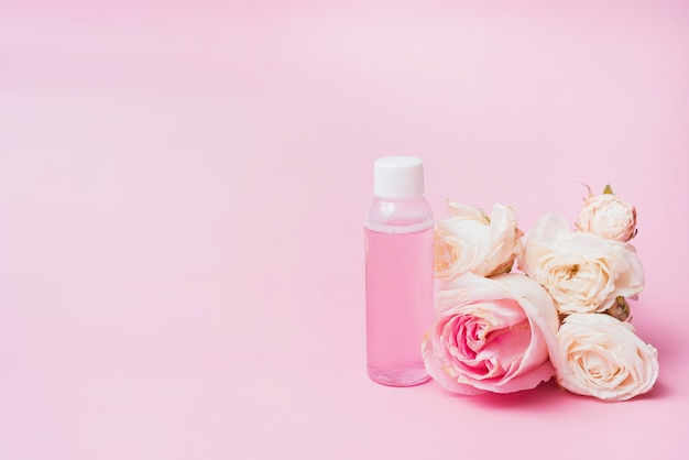 Pink water with rose extracts on a background of flower with copy space Premium Photo