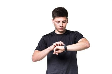 Portrait of a focused young sportsman adjusting his wristwatch isolated over white Free Photo