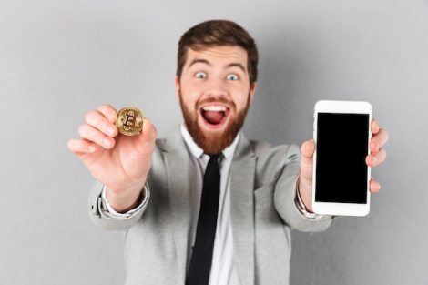 Portrait of a happy businessman holding bitcoin Free Photo