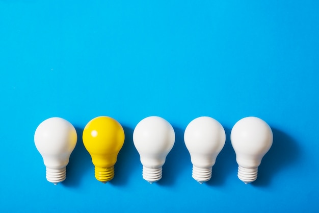 Row of white bulbs with yellow bulb on blue background Free Photo