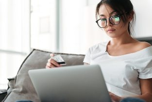 Serious young woman holding debit card using laptop computer. Free Photo