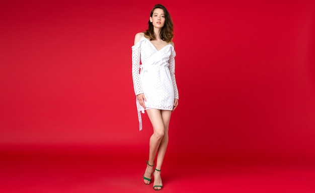 Sexy stylish woman in summer fashion trend white dress posing on red studio Free Photo