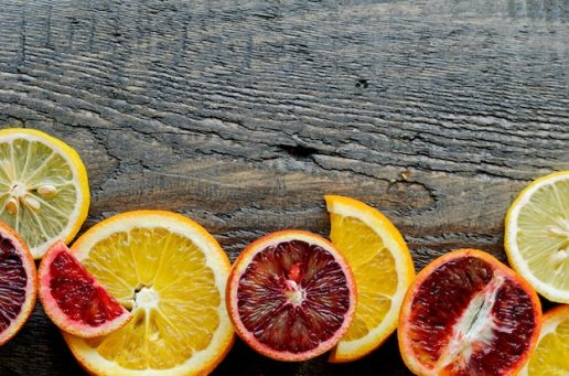Sliced and cut sicilian blood oranges on wooden natural background, top view Premium Photo