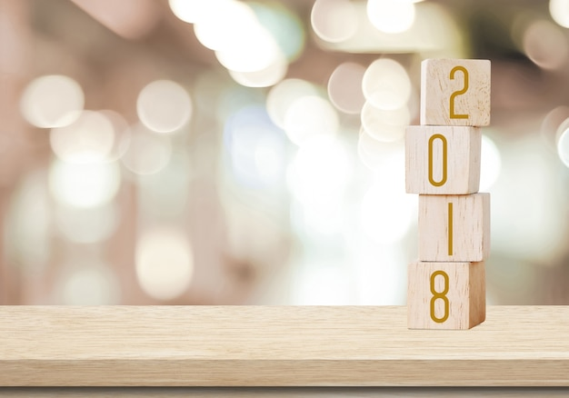 Wooden cubes with 2018 on perspective wood over blur bokeh     Wooden cubes with 2018 on perspective wood over blur bokeh background with  copy space for text