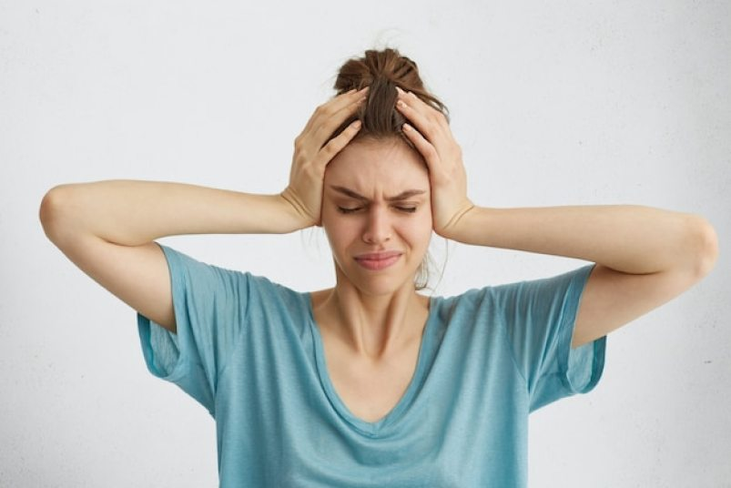 Worried woman closing her eyes with hands on head having headache Free Photo