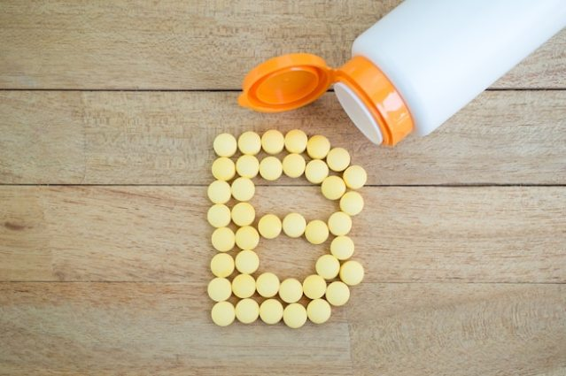 Yellow pills forming shape to b alphabet on wood background Premium Photo