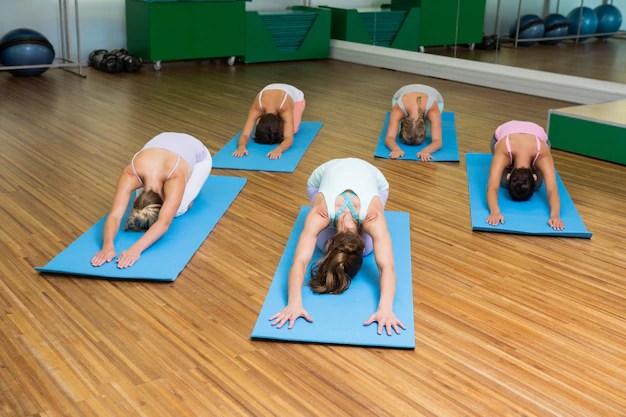 Yoga class in childs pose in fitness studio Premium Photo
