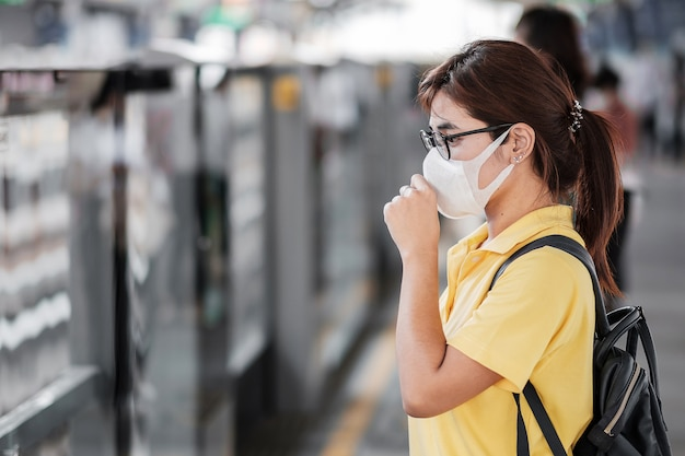 Young asian woman wearing protection mask against novel coronavirus (2019-ncov) or wuhan coronavirus at public train station,is a contagious virus that causes respiratory infection.healthcare concept Premium Photo