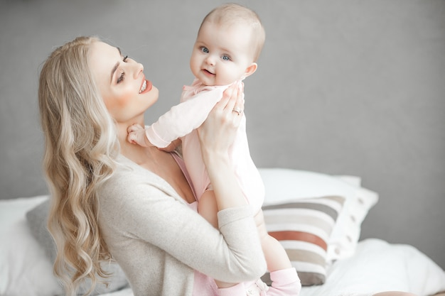 Premium Photo Young Mother Taking Care Of Her Little Baby Girl Beautiful Mom And Her Daughter Indoors In The Bedroom Loving Family Attractive Mum Holding Her Child