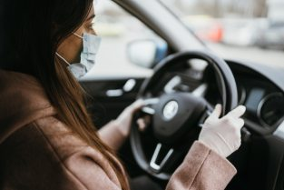 Young woman in a mask and gloves driving a car. Free Photo