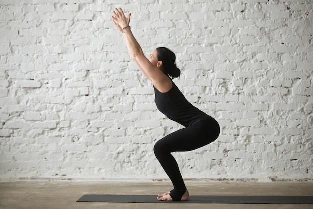 Young yogi attractive woman in Utkatasana pose, white loft backg Free Photo