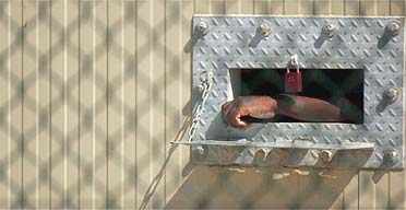 A detainee's arm hangs outside his cell at Camp Delta in Guanta