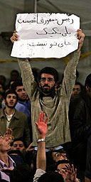 An Iranian student holds a placard, reading: