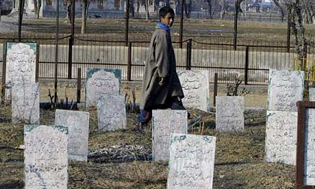 A Kashmiri boy walks in a graveyard in Srinagar, India