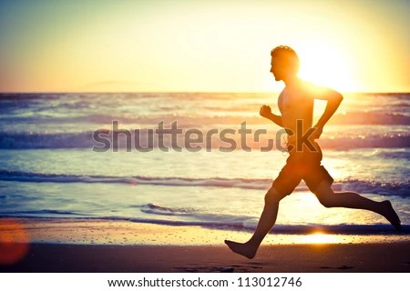 stock photo : Man running on the beach at sunset