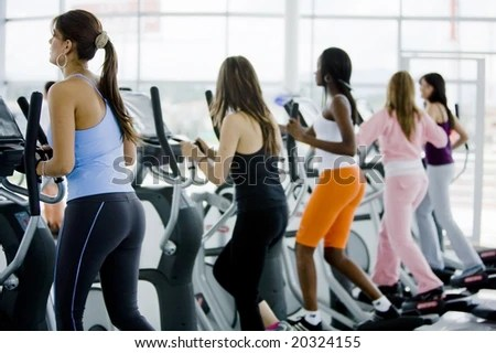 stock photo : group of women at the gym doing exercise on the xtrainer machines